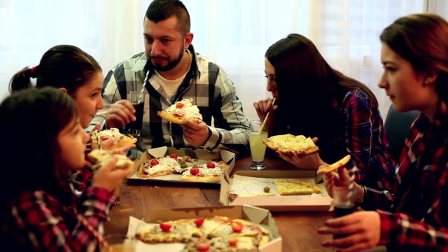 vídeos de stock, filmes e b-roll de família ou amigos, compartilhar uma pizza - irmão