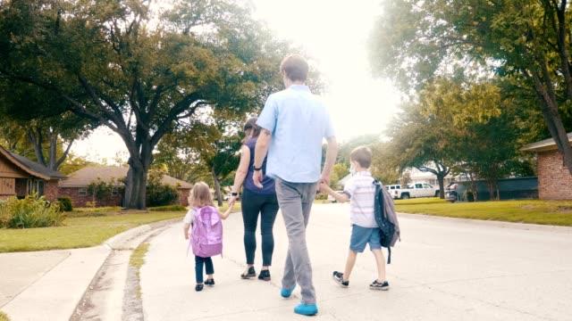 stockvideo's en b-roll-footage met familie uit voor een wandeling in hun buurt tijdens de covid-19 pandemie - zus