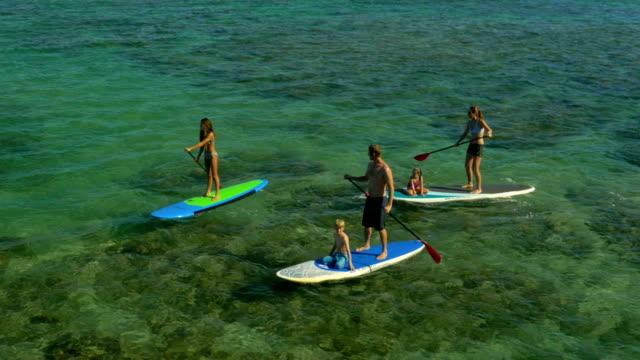 vídeos y material grabado en eventos de stock de familia de remo en una playa tropical vacaciones en hawai. - deporte acuático