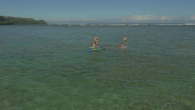 Familie peddel instappen op een tropisch strandvakantie naar Hawaï