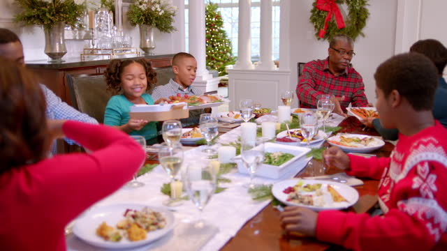 Family pass plates around table for Christmas dinner, cute young girl smells sweet potatoes hungrily as father serves them (dolly-shot)