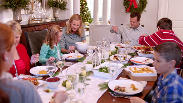 family pass plates around table for christmas dinner, mother scoops mashed potatoes onto young daughter's plate (dolly-shot) - lunch stock videos & royalty-free footage