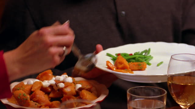 a family passes a bowl of sweet potatoes at the dinner table. - evening meal stock videos and b-roll footage