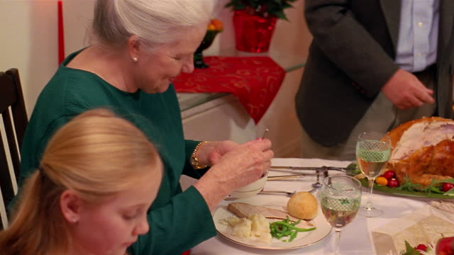 A family passes cranberry sauce around the dinner table at Christmas.