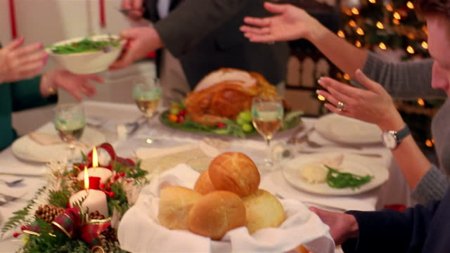 A family passes plates of food during Christmas dinner.