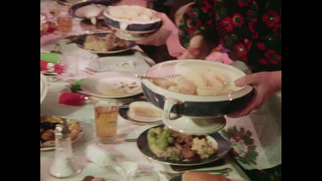 family passes serving dishes around at christmas - stereotypical stock videos & royalty-free footage