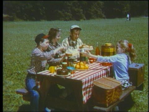 1960 family passing food at picnic table
