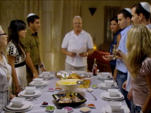 ws zi r/f ms family passing kiddush cup during sabbath / beit yitzhak, israel - 30 34 ��r bildbanksvideor och videomaterial från bakom kulisserna