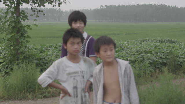 a family pauses near a field in china. - two generation family stock videos & royalty-free footage