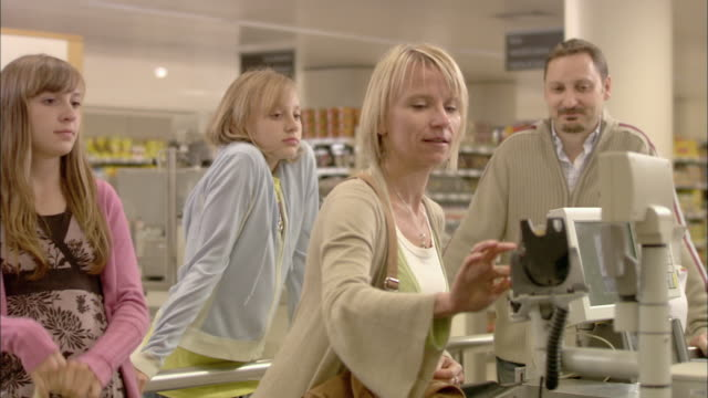 stockvideo's en b-roll-footage met ms family paying at checkout with credit card and receiving long receipt from cashier / north finchley, london, uk - lang lengte