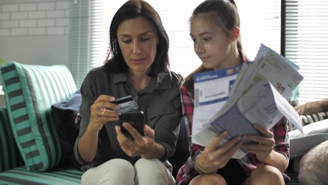vídeos de stock, filmes e b-roll de contas pagando da família em linha no telefone esperto - batendo com a cabeça na parede