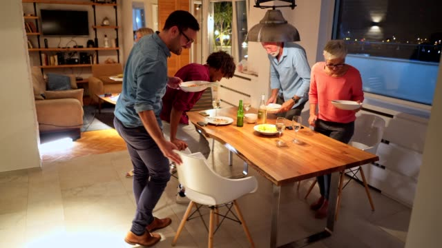 family picking up dishes after a finished dinner - guest stock videos & royalty-free footage