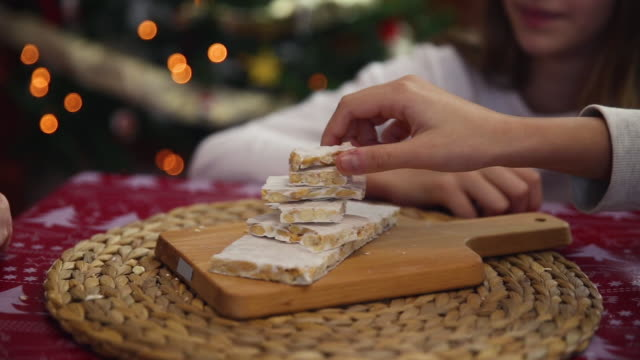 vídeos de stock e filmes b-roll de family picking up pieces of almond nougat with christmas tree lights behind - comida doce