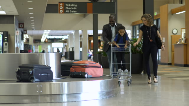vídeos y material grabado en eventos de stock de family picking up their luggage at an airport - diez segundos o más