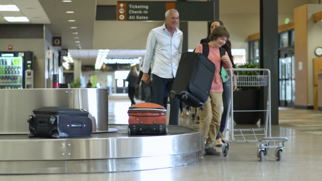 family picking up their luggage at an airport - 10 seconds or greater stock videos & royalty-free footage