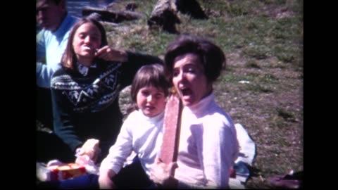 vidéos et rushes de 1969 family picnic on a lake, mom hams it up with large sausage - film d'amateur