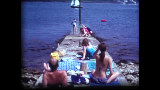 vídeos de stock, filmes e b-roll de 1973 family picnic on jetty watching sailboats - 1973
