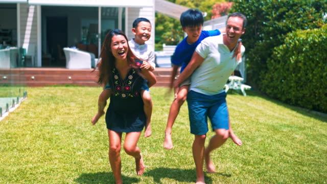 family piggyback ride - domestic garden stock videos & royalty-free footage