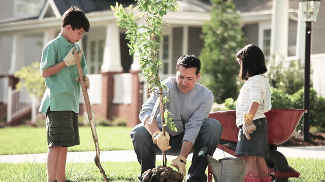 Family planting a tree in front yard of their home