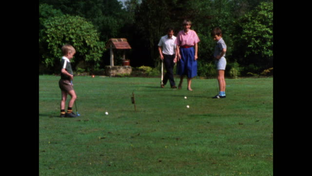family play miniature golf on grass course; 1986 - family with two children stock videos & royalty-free footage