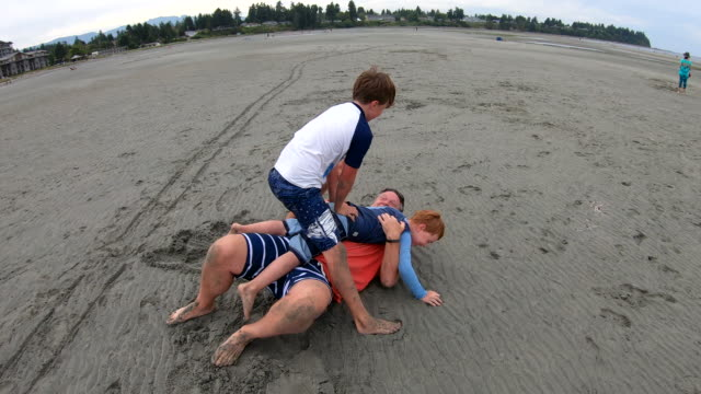 vidéos et rushes de jeu de famille sur la plage sablonneuse énorme ensemble - jouer à la bagarre
