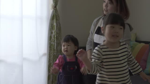 family playing and watching tv in the living room together - förälder och barn bildbanksvideor och videomaterial från bakom kulisserna