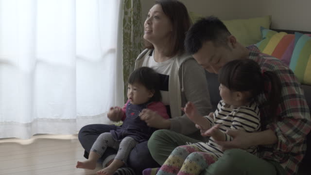 stockvideo's en b-roll-footage met family playing and watching tv in the living room together - in kleermakerszit