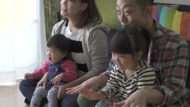 family playing and watching tv in the living room together - 絆点の映像素材/bロール