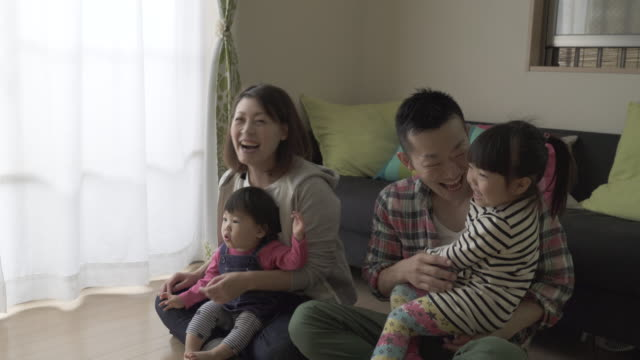 family playing and watching tv in the living room together - リビング点の映像素材/bロール