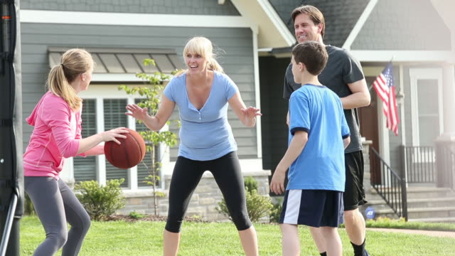 Family playing basketball in front of suburban house.
