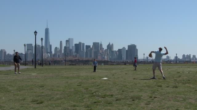 Family Playing Catch Together - Manhattan Skyline, Freedom Tower, Ellis Island