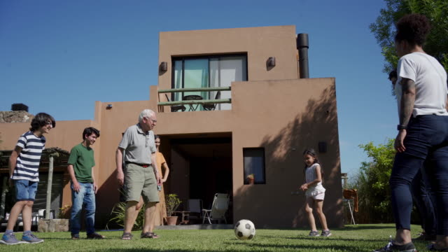 family playing football together - persona attraente video stock e b–roll