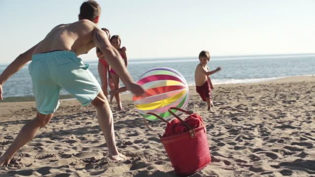 vídeos de stock, filmes e b-roll de family playing football with beach ball on beach. - bolsa tiracolo bolsa