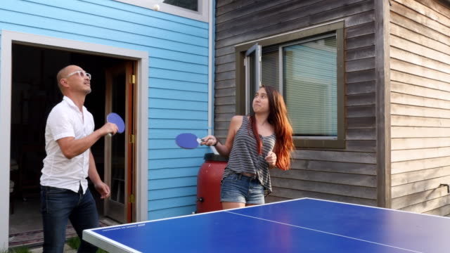 ms pan family playing game of ping pong in backyard of home on summer evening - bordtennis bildbanksvideor och videomaterial från bakom kulisserna