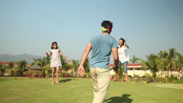 vidéos et rushes de family playing in a park  - pelouse