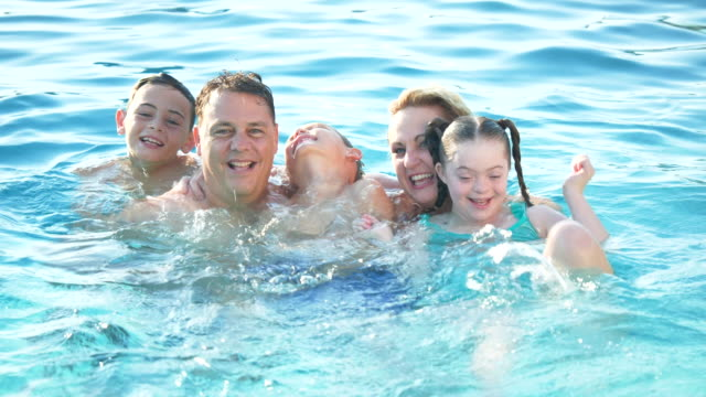 family playing in pool, girl with down syndrome - 10 11 years stock videos & royalty-free footage