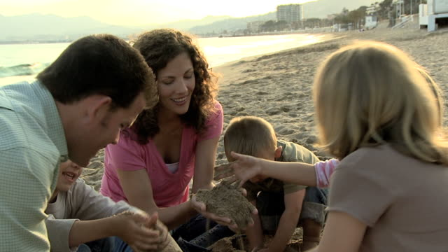 vídeos de stock e filmes b-roll de family playing in the sand on the beach together in a circle - família com quatro filhos
