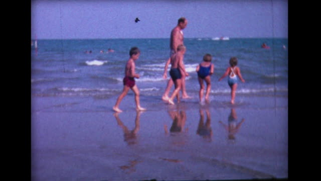 1964 family playing in the shallows - reifenschlauch stock-videos und b-roll-filmmaterial