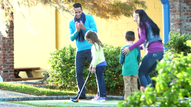 family playing miniature golf, putting into hole - 25 29 years stock videos and b-roll footage