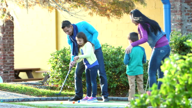 Family playing miniature golf, putting into hole