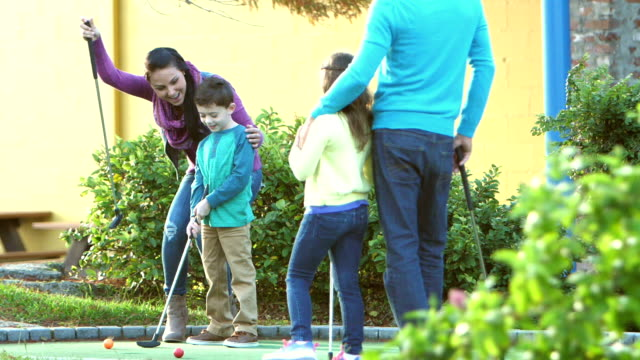vídeos de stock e filmes b-roll de family playing miniature golf, putting into hole - 6 7 years