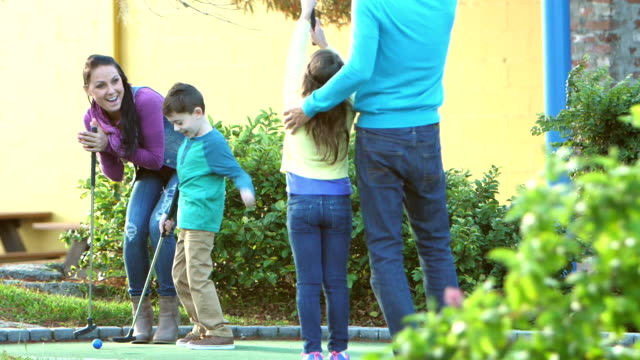 family playing miniature golf, putting into hole - 6 7 years stock videos & royalty-free footage