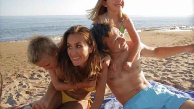 family playing on beach - 水泳パンツ点の映像素材/bロール