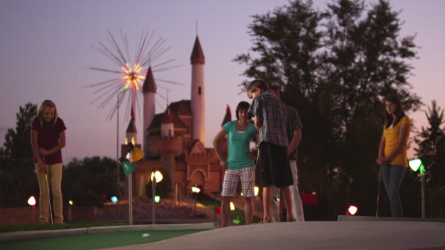 vídeos de stock e filmes b-roll de ws family playing on miniature golf course, boy (10-11) making putt into hole / orem, utah, usa - orem