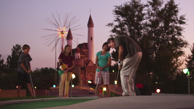 ws family playing on miniature golf course, man giving high-five after scoring / orem, utah, usa - minigolf stock-videos und b-roll-filmmaterial