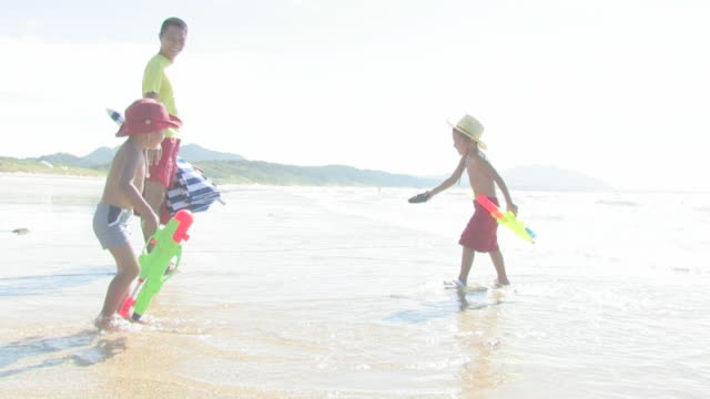 stockvideo's en b-roll-footage met family playing on shore - 2 3 jaar