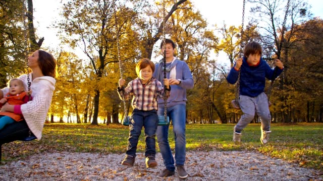 SLO MO Family playing on swings in the park