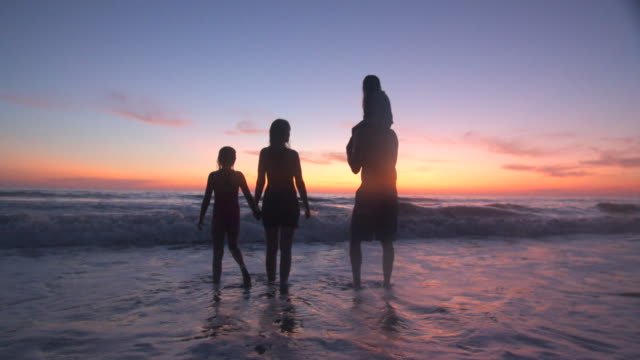 family playing on the beach at sunset - auf den schultern stock-videos und b-roll-filmmaterial