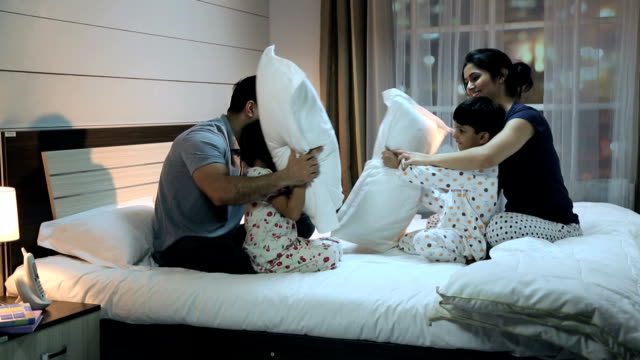 family playing pillow fight on the bed, delhi, india - 枕投げ点の映像素材/bロール