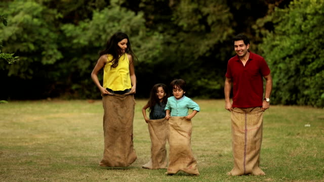family playing sack race in park, delhi, india - sack race stock videos & royalty-free footage